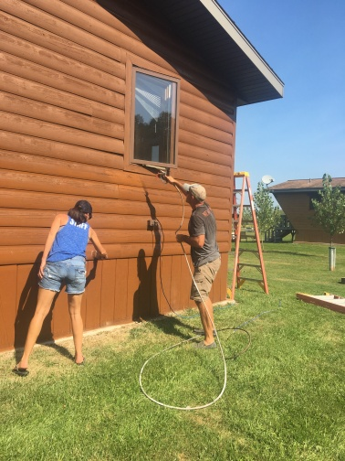 Resort ownership requires ongonig maintenance. Owners Lisa and Jason Goulet update the exteriors of one of the cabins.